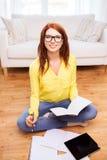 Adolescente de sourire avec le PC de comprimé à la maison Photos stock