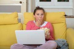 Adolescente de sourire employant l'ordinateur portable et manger du maïs éclaté photos libres de droits