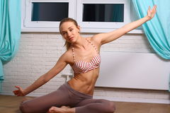 Adolescente de sourire faisant l'exercice sur le plancher à la maison Images stock