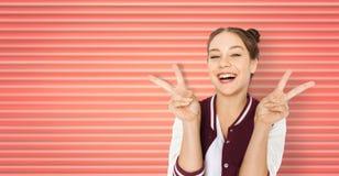 Adolescente de sourire heureuse montrant le signe de paix photos stock