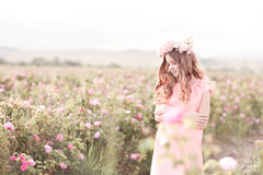 Adolescente de sourire se tenant dans la roseraie Image stock