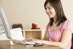 Adolescente de sourire sur l'ordinateur à la maison Images stock