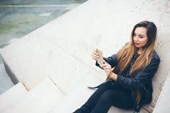 Adolescente de sourires de Beautuful la jeune avec les cheveux très longs s'assied sur les pas concrets et fait la photo de selfi Photographie stock