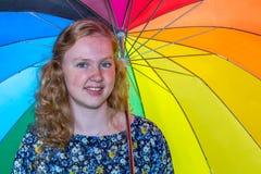 Adolescente debajo del paraguas coloreado Fotos de archivo