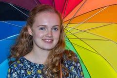 Adolescente debajo del paraguas con diversos colores Fotos de archivo