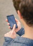 Adolescente dei pantaloni a vita bassa che per mezzo di uno Smart Phone all'aperto Fotografia Stock