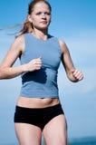 Adolescente del deporte que se ejecuta sobre el cielo azul Imagen de archivo libre de regalías