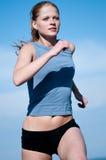 Adolescente del deporte que se ejecuta sobre el cielo azul Imagenes de archivo