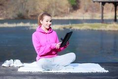 Adolescente del deporte que usa el panel táctil de la tableta en el embarcadero Fotografía de archivo libre de regalías