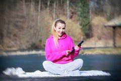 Adolescente del deporte que usa el panel táctil de la tableta en el embarcadero Fotos de archivo