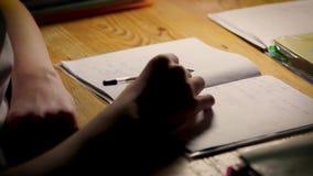 Adolescente del escolar que estudia haciendo su preparación Muchacho que se sienta en la tabla y que escribe en sus notas en el t metrajes