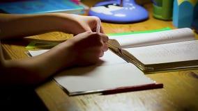 Adolescente del escolar que estudia haciendo su preparación Muchacho que se sienta en la tabla y que escribe en sus notas en el t almacen de video