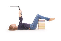 Adolescente del estudiante que miente de lado en el piso con el ordenador portátil Imagenes de archivo