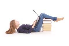 Adolescente del estudiante que miente de lado en el piso con el ordenador portátil Fotos de archivo