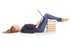 Adolescente del estudiante que miente de lado en el piso con el ordenador portátil Imagen de archivo