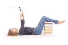 Adolescente del estudiante que miente de lado en el piso con el ordenador portátil Foto de archivo