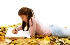 Adolescente del estudiante que se acuesta con las hojas alrededor Foto de archivo libre de regalías