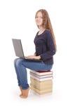 Adolescente del estudiante que se sienta de lado en el libro con el ordenador portátil Fotos de archivo libres de regalías