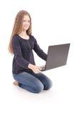 Adolescente del estudiante que se sienta de lado en el piso con el ordenador portátil Foto de archivo