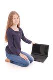 Adolescente del estudiante que se sienta de lado en el piso con el ordenador portátil Imagen de archivo libre de regalías