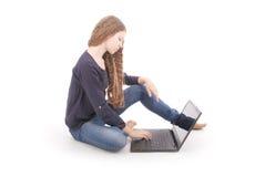 Adolescente del estudiante que se sienta de lado en el piso con el ordenador portátil Fotografía de archivo
