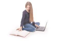 Adolescente del estudiante que se sienta de lado en el piso con el ordenador portátil Imagenes de archivo