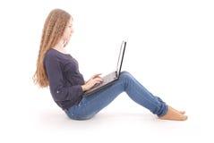 Adolescente del estudiante que se sienta de lado en el piso con el ordenador portátil Fotos de archivo