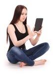 Adolescente del estudiante que se sienta de lado en el piso con la tableta p Imágenes de archivo libres de regalías