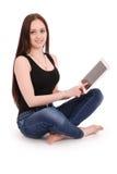Adolescente del estudiante que se sienta de lado en el piso con la tableta p Foto de archivo libre de regalías