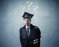 Adolescente del graduado joven con los signos de interrogación dibujados Imagen de archivo libre de regalías