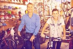 Adolescente del hombre y del muchacho que compra la nueva bicicleta en tienda del deporte Fotos de archivo