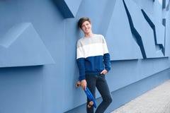 Adolescente del inconformista con el monopatín cerca de la pared Fotografía de archivo libre de regalías