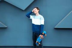 Adolescente del inconformista con el monopatín cerca de la pared Fotos de archivo