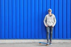 Adolescente del inconformista con el monopatín cerca de la pared del color Imagen de archivo libre de regalías