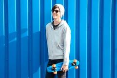Adolescente del inconformista con el monopatín cerca de la pared del color Imágenes de archivo libres de regalías