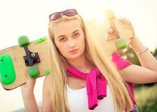 Adolescente del inconformista con el monopatín, imagen con el sunflare Imagenes de archivo