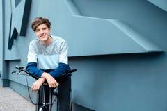 Adolescente del inconformista con la bicicleta cerca de la pared Imagenes de archivo