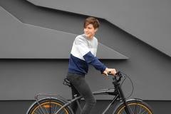 Adolescente del inconformista con la bicicleta cerca de la pared Foto de archivo