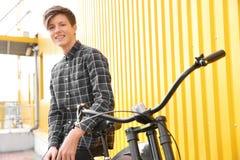 Adolescente del inconformista con la bicicleta cerca de la pared del color Imagen de archivo libre de regalías