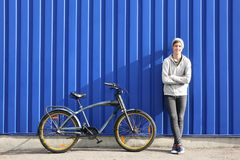 Adolescente del inconformista con la bicicleta cerca de la pared del color Foto de archivo libre de regalías
