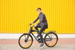 Adolescente del inconformista con la bicicleta cerca de la pared del color Fotos de archivo libres de regalías