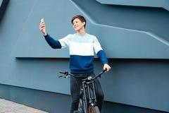 Adolescente del inconformista con la bicicleta que toma el selfie cerca de la pared Foto de archivo