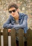 Adolescente del inconformista con las gafas de sol sobre una cerca Fotografía de archivo