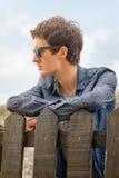 Adolescente del inconformista con las gafas de sol sobre una cerca Foto de archivo