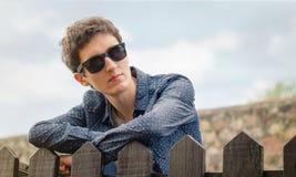 Adolescente del inconformista con las gafas de sol sobre una cerca Fotos de archivo