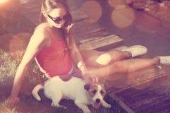 Adolescente del inconformista con su perro que miente en la hierba Fotografía de archivo