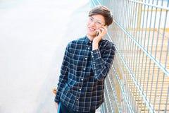 Adolescente del inconformista que habla en el teléfono cerca de la cerca Imagen de archivo libre de regalías
