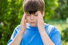 Adolescente del muchacho con dolor de cabeza en la naturaleza Imagenes de archivo
