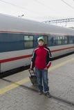 Adolescente del muchacho con el bolso del viaje cerca de un tren Imágenes de archivo libres de regalías