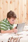 Adolescente del muchacho con el ordenador de la tablilla Imágenes de archivo libres de regalías